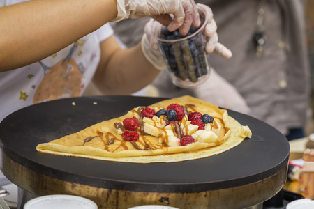 Close-up of hands of cook in gloves preparing Crepe, pancake on frying pan with fresh banana, blueberry, raspberry, sweet sauce. Concept very tasty fast food Stock Photo