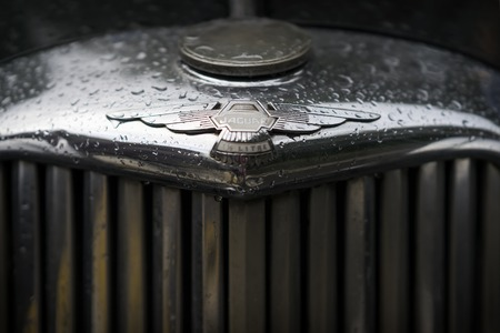 MOSCOW, RUSSIA - AUGUST 26, 2017: Jaguar car emblem on a vintage dark car close-up. Retro cars festival. Rainy evening Editorial