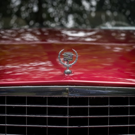 MOSCOW, RUSSIA - AUGUST 26, 2017: Close-up of Cadillac car logo on a vintage car, selectiv focus. Retro cars festival. Rainy evening, red square
