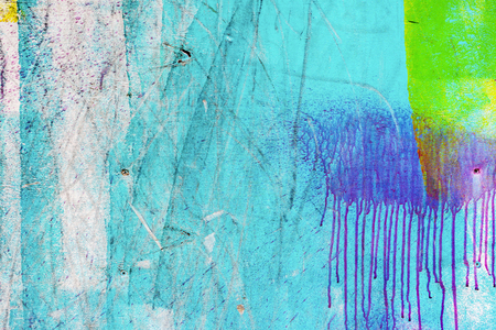 Close-up of abstract dirty painted wooden surface, flowing paint of different bright colors, as graffiti. Colorful grunge texture of wall. Abstract modern background Stock Photo