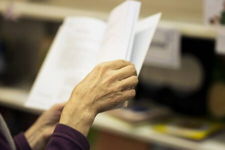 Close-up of hands of the elderly person with open book, bookstore. Real scene. Education concept, Self-study, reading fiction, pension, interests in elderly, life style Foto de archivo