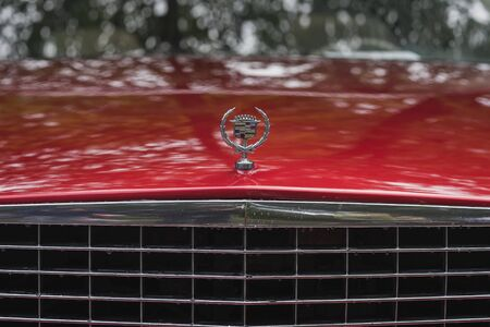 MOSCOW, RUSSIA - AUGUST 26, 2017: Close-up of Cadillac car logo on vintage car, selectiv focus. Retro car show exhibion, motor vehicles festival. Rainy evening, red