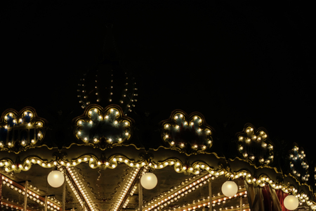 Illuminated golden bright carousel, silhouette on night city, romantic, nostalgic mood, melancholy, festive occasions, copy space