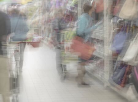 Shopping center, shop mall store. Woman in supermarket with shopping basket, retail. Abstract defocused motion blurred unrecognizable people. Background with copy space