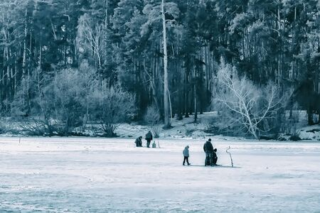 Winter fishing. River, lake near forest in ice. Anglers, Fishermens during your favorite leisure time. Toned image