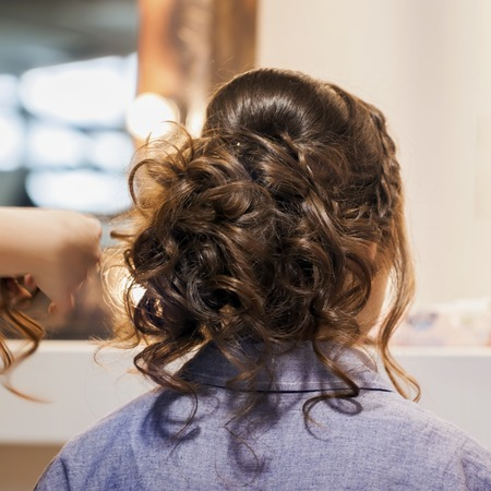 Unrecognizable girl back to us, young woman in mirror at hairdresser making hairstyle, styling from long hair in hair salon. Hands of master are partially visible