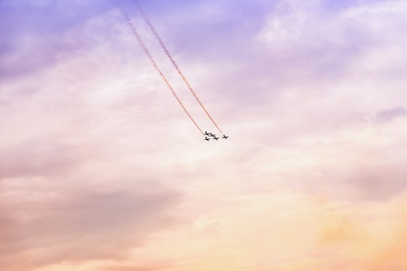 Group of aircraft flying at sunset. Exciting performance. Air performance, air show, aircrafts, flying display and skill teamwork. Abstract background