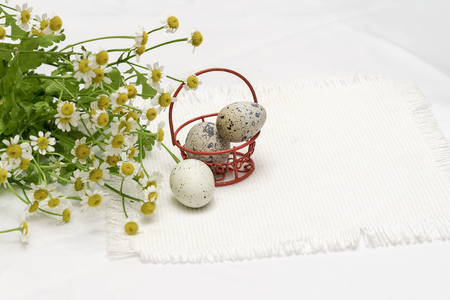 Quail eggs in red metallic basket and fresh flowers, daisies, light rustic napkin, top view. Concept for Easter, spring, organic food, dieting. Background, copy space Stock Photo