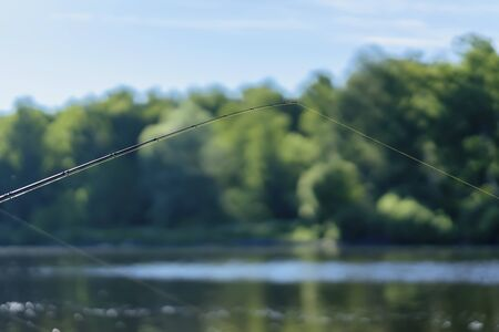 Summer landscape with fishing line on the background of lake, opposite shore, morning, selective focus. Copy space