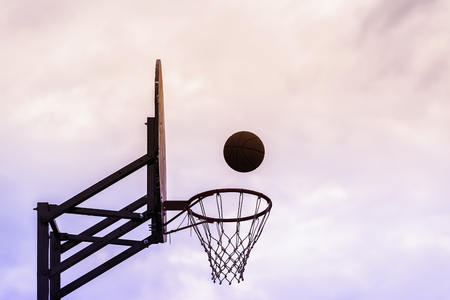 Graphic photo of Basketball shield, ball flying to basket on background of sky. Concept of sport, hit accuracy. Copy space