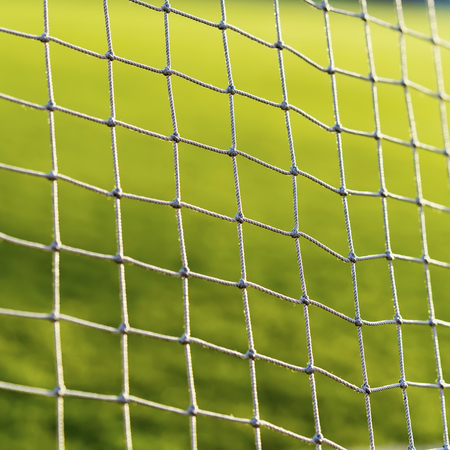 Soccer net on green live, on background of green grass close-up Stock Photo