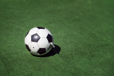 Old, dirty tattered soccer ball on background of green grass. Traditional classic black and white football ball on green field of the stadium training, playground, copy space