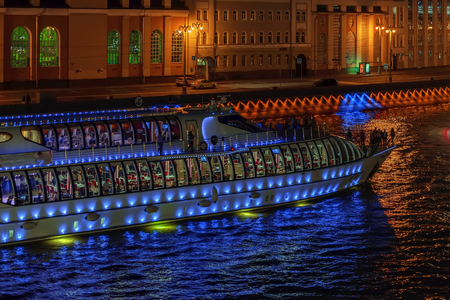 Abstract illuminated ship for travels, excursions with unrecognizable silhouettes of tourists at night in the city