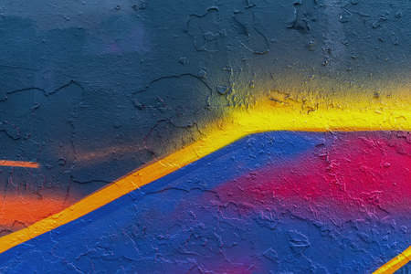 Abstract bright fragment of wall with old chipped paint, scratch, grunge texture. Aerosol design, yellow, blue, pink shades. Modern background, banner design Banco de Imagens