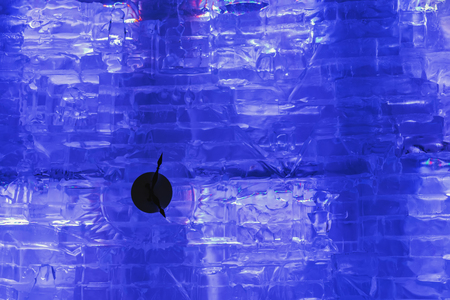 Winter ice time , time clock on an icy wall with purple LED lighting. Winter holiday, Happy New Year, xmas.