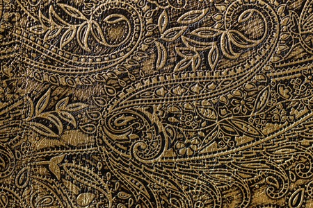 Texture of golden brown genuine leather close-up, with embossed floral trend pattern, wallpaper or banner design Stock Photo