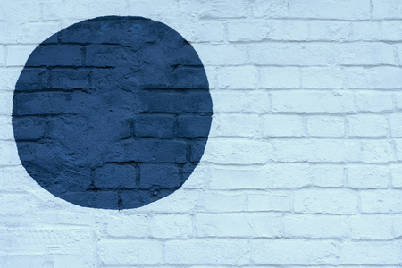 Drawn painted dark blue circle on light blue brick wall bricks surface of wall, as graffiti. Graphic grunge texture. Abstract background, stylish pattern