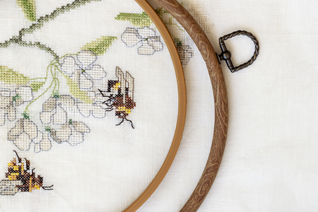 Wooden embroidery hoop with fragment of a colorful cross-stitch embroidery, summer flower ornament. Top view