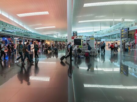 BARCELONA, SPAIN - June 08, 2019. El Prat Josep Tarradellas Airport. Public area, Terminal T1. Walking and sitting passengers, waiting for flights inside modern airport Imagens - 129584071