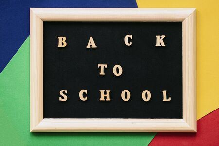 Back to school text written wooden letters on black blackboard in frame. Concept of education, starting school. Colorful background