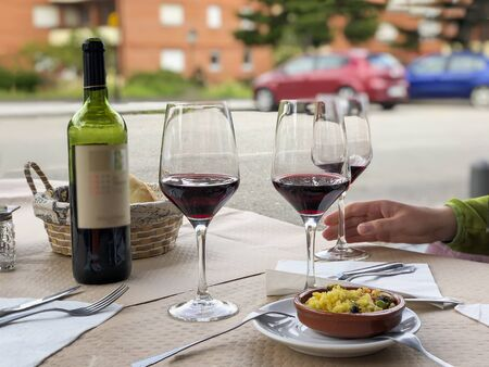 Three glasses of red wine, bottle of wine and chefs compliment, small plate of paella served on table outdoor terrace. Summer evening