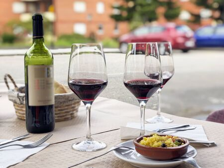 Three glasses of red wine, bottle of wine and chefs compliment, small plate of paella served on table outdoor terrace