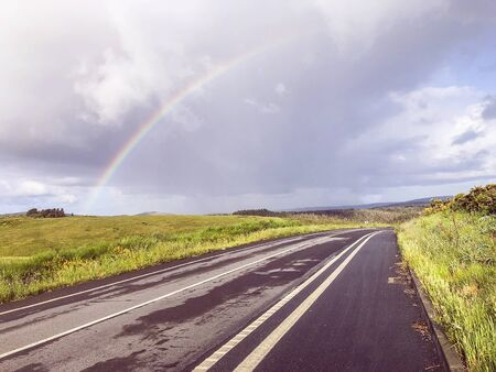 Empty asphalt road among the deserted rolling fields, natural landscape, way with rainbow