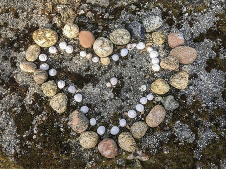 Heart shape from stones and shells on natural ground. Romantic love symbol, Valentine concept, top view