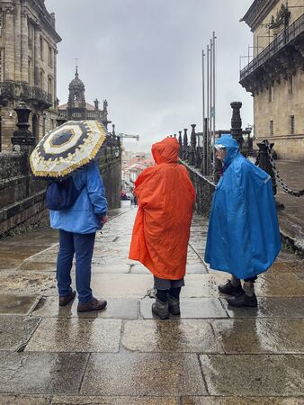Three pilgrims back to us, with backpacks in colorful raincoats with an umbrellas standing in the historic square Imagens