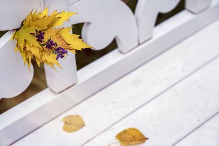 Bright autumn bouquet of fallen leaves and violet flower close-up in white bench in park, sunny day, autumn natural background. Selective focus, copy space