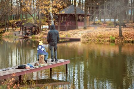 Adult and child on a wooden pier, fishing bridge. Autumn park. Fallen leaves, sunny day, natural background.