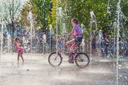 Summer, heat, a girl riding a bike among fountains, people cool in jets of water