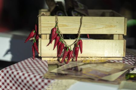 Fresh organic red fresh chili pepper on a string on wooden box, real still life in farmers market