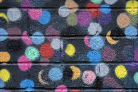 Bricks wall is decorated with bright abstract colored circles on black background closeup. Detail like as graffiti . Fragment for background, stylish picture Imagens - 129626132