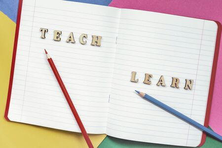 Teach and learn, words in open notebook, colored paper sheets. Concept of education, starting school, back to school. Colorful background Imagens - 129626135