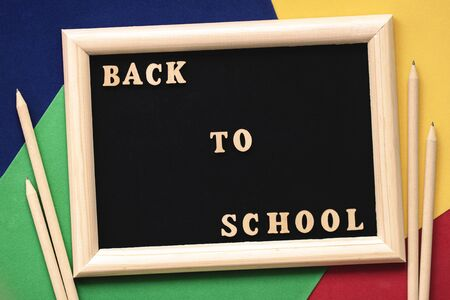 Back to school text, wooden letters in black background, frame on colored paper sheets, pencils. Concept of education, starting school. Background with copy space Stock Photo
