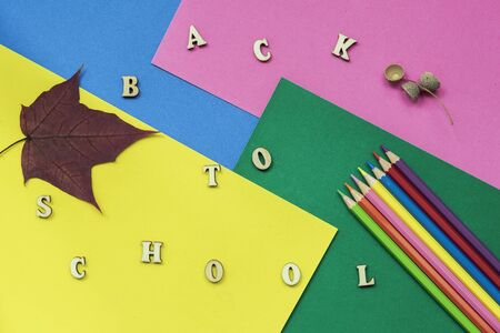 Colorful crayons, maple leaf and Back to school text, wooden letters on colored paper sheets. Concept of education, starting school Imagens - 129626149