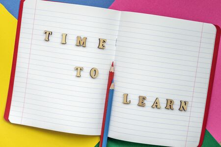 Time to learn, text and colorful crayons in an open notebook. Concept of education, starting school, back to school.