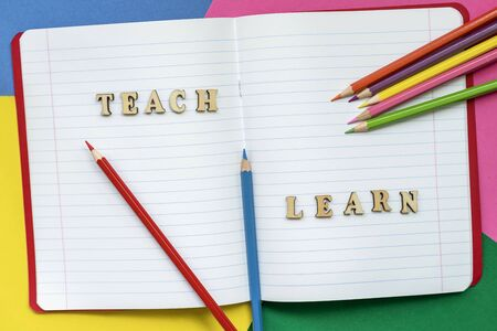 Teach and learn, words in open notebook, colorful crayons and colored paper sheets. Concept of education, starting school