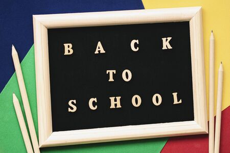 Back to school text, wooden letters in black background, frame on colored paper sheets, pencils. Concept of education, starting school