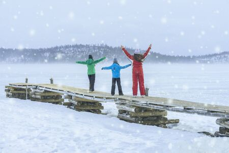Three girls of different ages and height in colorful winter suits with snowflakes on nature on a cold day, games and leisure in winter Imagens - 129626172