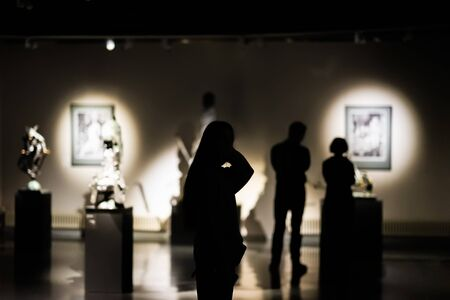Silhouettes of unrecognizable people, visitors to an art gallery, a museum with paintings, selective focus Imagens - 129626175