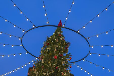 Christmas tree on the street in the lights and garlands against the sky