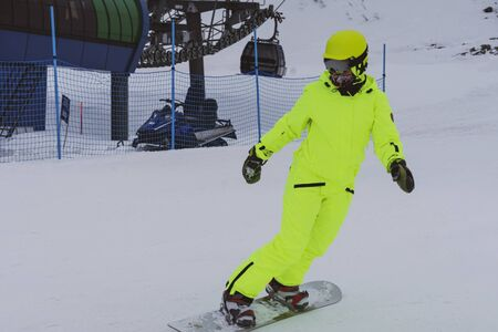 Snowboarder skiing in bright yellow suit, overalls Imagens