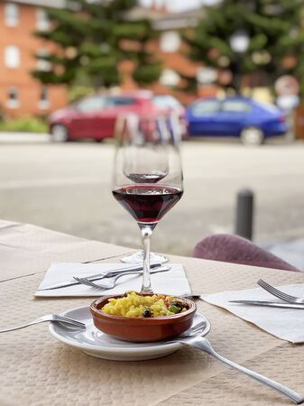 Two near glasses of red wine, bottle of wine and chefs compliment, small plate of paella served on table outdoor terrace. Vertical blurred background Imagens - 129626225