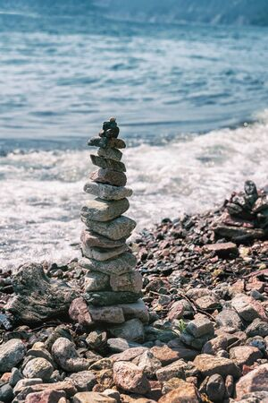 Pyramid of pebbles on the beach on a background of the sea wave. Stability, balance and harmony, vacation at sea
