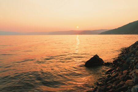 Picturesque sunset in golden orange colors on a rocky beach, late summer evening