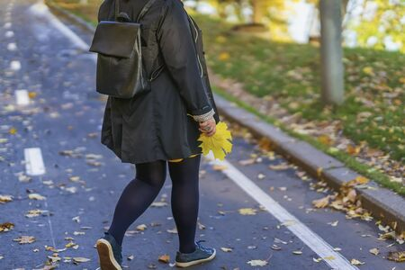 Unrecognizable girl back to us is walking in the autumn park park along the paths among the fallen leaves and pick them Imagens