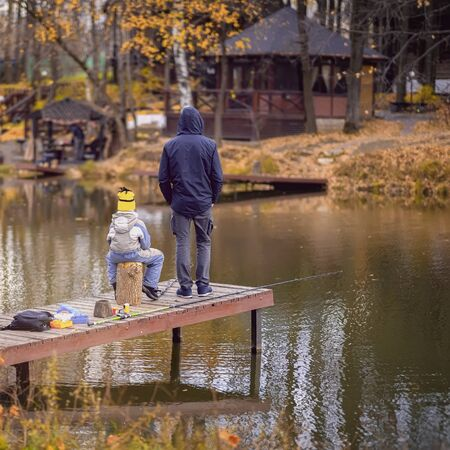 Autumn fishing, unrecognizable men and child, backs to us. Wooden pier, fishing bridge. Autumn park. Fallen leaves, sunny day, natural background. Imagens