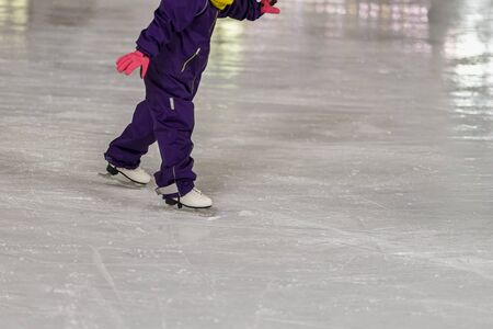 Small child in overalls learn to skate outdoors at the rink in the winter park